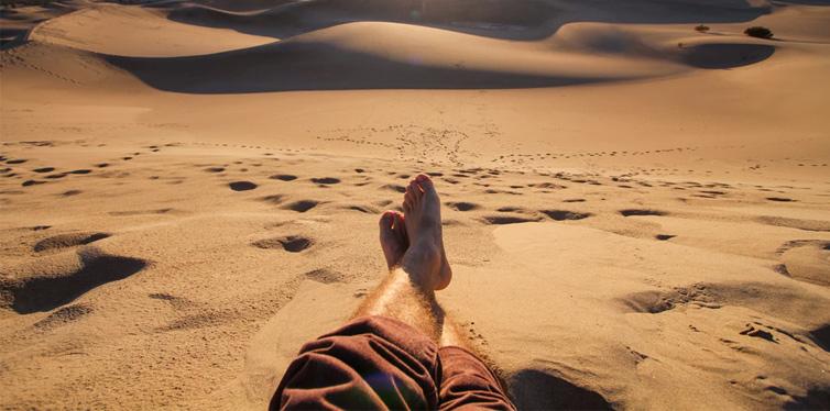 mans feet on the sand