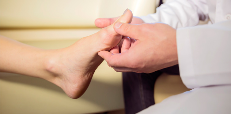 a doctor holding patients foot