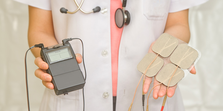 doctor holding tens machine