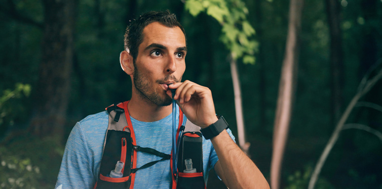 male runner drinking from a hydration backpack