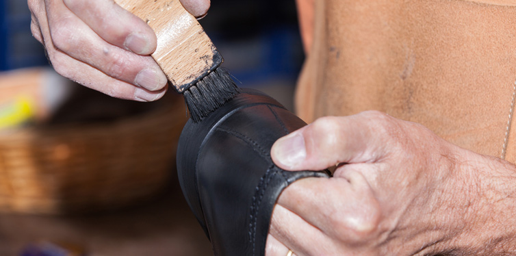 shoemaker puts polish on shoes