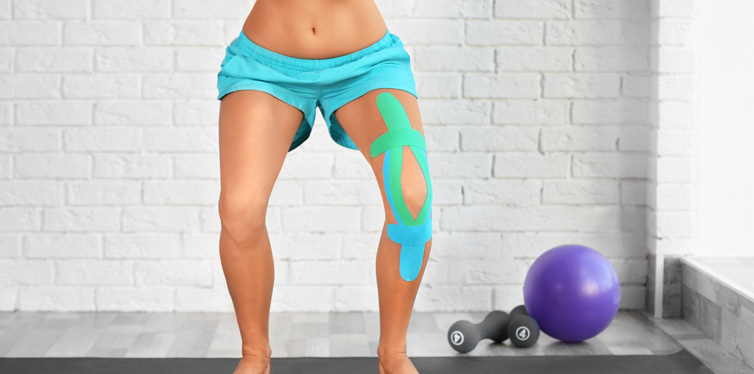woman with elastic tape around her knee